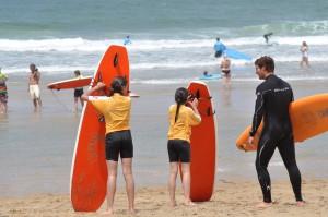 enroulage de leash sur la plage apres une lesson de surf